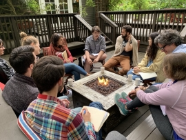 Retreat goers seated around patio fire pit